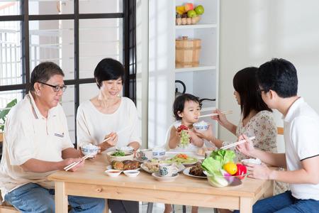 Aziatische familie het eten van thuis. Multi generatie hebben maaltijd, levend levensstijl. Stockfoto