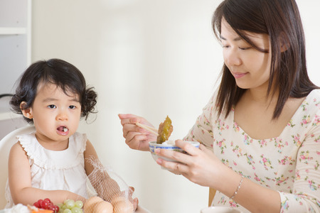 hungry children: Asian mother feeding her child at home. Family living lifestyle. Stock Photo