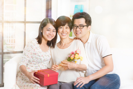 three presents: Happy mothers day. Asian senior mom received gift box and flowers from her young children. Family living lifestyle at home. Stock Photo