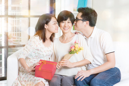 three gift boxes: Happy mothers day. Asian boy and girl kissing mother. Family living lifestyle at home. Stock Photo