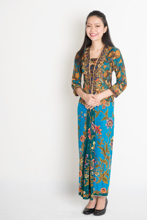 Full length Southeast Asian female in batik dress standing on plain background.