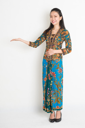 adult indonesia: Full length portrait of Southeast Asian woman in batik dress hand holding something standing on plain background. Stock Photo
