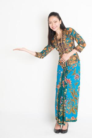Full length portrait of Southeast Asian girl in batik dress hand holding something standing on plain background.