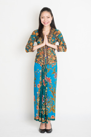 Full length Southeast Asian woman with batik dress in greeting gesture standing on plain background.