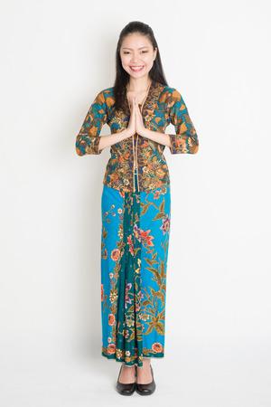 batik: Pleine longueur Sud-femme asiatique avec robe de batik en guise de salutation geste debout sur fond uni.