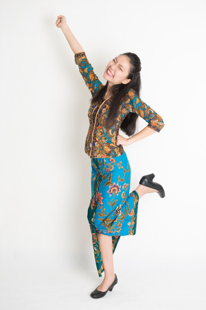 Full length portrait of Southeast Asian female in batik dress arms up, cheering and jumping around on plain background.