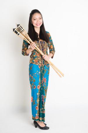 girl in dress: Full body portrait of Southeast Asian girl in batik dress hands holding oil lamp torch standing on plain background. Stock Photo