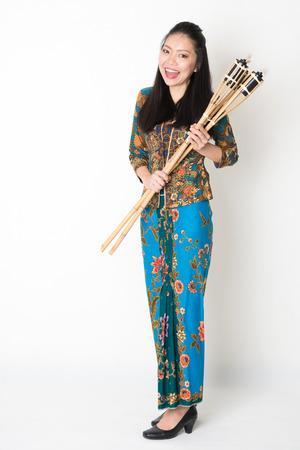 pelita: Full body portrait of Southeast Asian girl in batik dress hands holding bamboo torch standing on plain background. Stock Photo