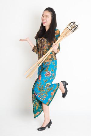 pelita: Full body portrait of happy Southeast Asian woman in batik dress hand holding bamboo oil lamp standing on plain background.