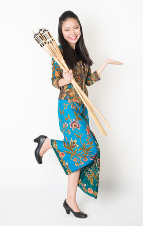 pelita: Full body portrait of Southeast Asian woman in batik dress hand holding bamboo oil lamp showing something standing on plain background.