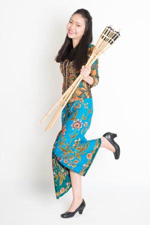 pelita: Full body portrait of Southeast Asian woman in batik dress hand holding pelita or oil lamp standing on plain background. Stock Photo