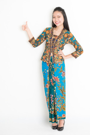 Full body portrait of Southeast Asian woman in batik dress giving thumb up, standing on plain background. Imagens
