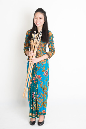 Full body portrait of Southeast Asian girl in batik dress hands holding pelita standing on plain background.