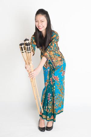 pelita: Full body portrait of Southeast Asian woman in batik dress hands holding pelita standing on plain background.