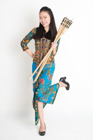 pelita: Full body portrait of Southeast Asian woman in batik dress hands holding bamboo oil lamp standing on plain background. Stock Photo