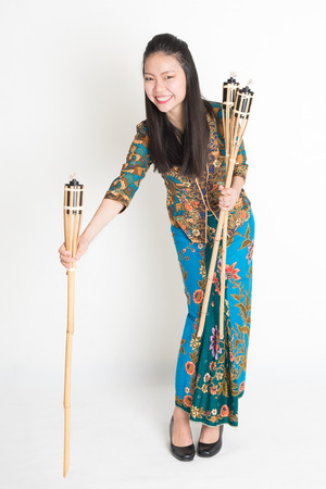 hari raya aidilfitri: Full body portrait of Southeast Asian woman in batik dress hands holding tiki torch standing on plain background. Stock Photo