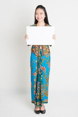 one female: Full body portrait of Southeast Asian girl in batik dress hands holding white blank placard, standing on plain background.
