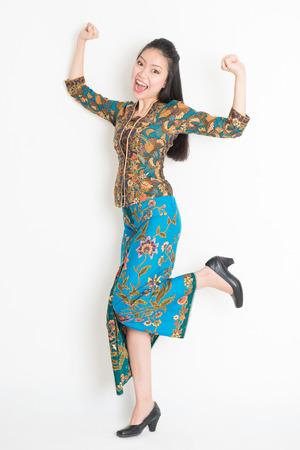 batik: Portrait d'une jeune fille asiatique du Sud-Est en batik bras robe jusqu'à heureuse sauter autour, pleine longueur debout isolé sur fond uni.