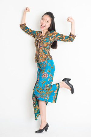Portrait of an Southeast Asian girl in batik dress arms up happy jumping around, full length standing isolated on plain background.