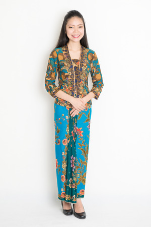 malay ethnicity: Full length Southeast Asian girl in batik dress standing on plain background.