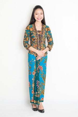 batik: Pleine longueur du Sud-Est asiatique fille en robe de batik debout sur fond uni. Banque d'images