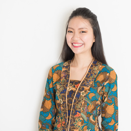 batik: Portrait of Southeast Asian woman in batik dress on plain background. Stock Photo