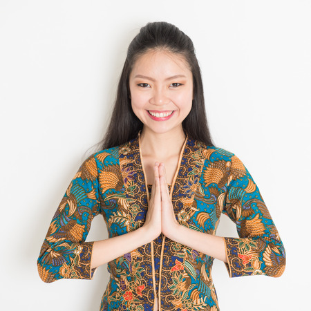 Portrait of happy Southeast Asian woman with batik dress in greeting gesture on plain background.