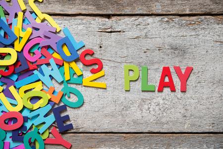 """Die bunten Worte """"PLAY"""" mit Holzbuchstaben neben einem Haufen von anderen Buchstaben über alte Holzplatte hergestellt."""