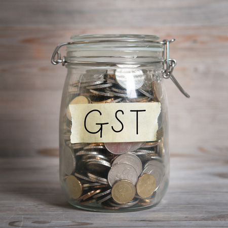 good investment: Coins in glass money jar with gst label, financial concept. Vintage wooden background with dramatic light. Stock Photo
