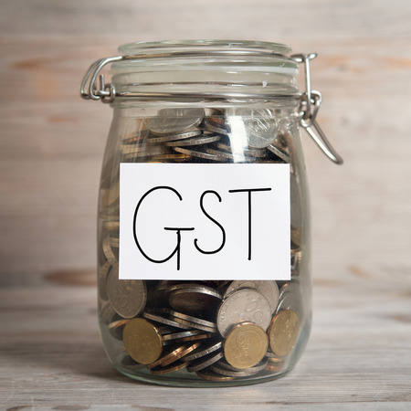 tax tips: Coins in glass money jar with gst label, financial concept. Old wooden background with dramatic light.