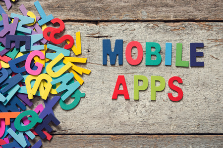 letter of application: The colorful words MOBILE APPS made with wooden letters next to a pile of other letters over old wooden board. Stock Photo