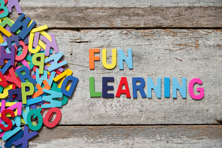 """Kleurrijke woorden """"FUN leanring"""" gemaakt met houten letters naast een stapel van andere brieven over oude houten bord."""