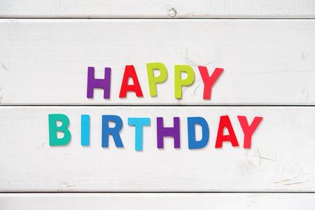 """joyeux anniversaire: Les mots colorés """"HAPPY BIRTHDAY"""" faite avec des lettres en bois sur le tableau blanc. Banque d'images"""