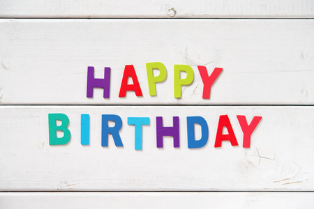 text space: The colorful words HAPPY BIRTHDAY made with wooden letters on white board. Stock Photo
