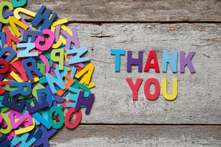 """Kleurrijke woorden """"dank u"""" gemaakt met houten letters naast een stapel van andere brieven over oude houten bord."""