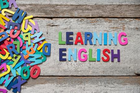 """učit se: Tyto barevné slova """"LEANRING angličtiny"""" vyrobené s dřevěnými písmeny vedle hromady dalších dopisů přes starou dřevěnou desku."""
