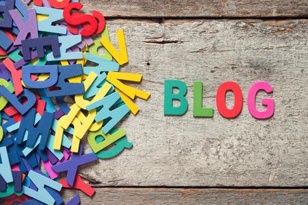 """Le mots colorés """"BLOG"""" fait avec des lettres en bois à côté d'un tas d'autres lettres plus vieille planche de bois."""