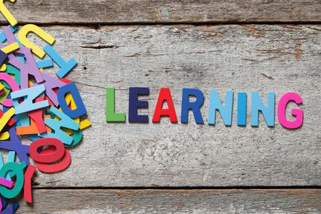 """De kleurrijke woorden """"LEARNING"""" gemaakt met houten letters naast een stapel andere letters over oud houten bord."""