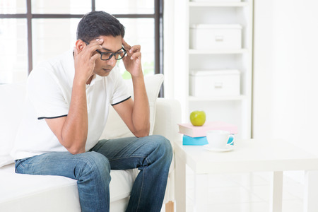 holding the head: Indian guy having headache at home. Asian man hands holding head sitting on sofa indoor. Handsome male portrait.