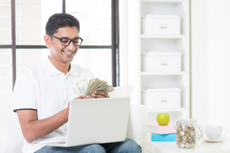 man working on computer: Indian guy counting cash, earning money from his successful online business. Asian man working from home. Stock Photo
