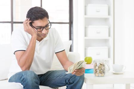 factura: Los problemas financieros concepto. Chico indio contar dinero con expresión triste, sentado en el sofá en casa. Varón asiático retrato de interior. Foto de archivo