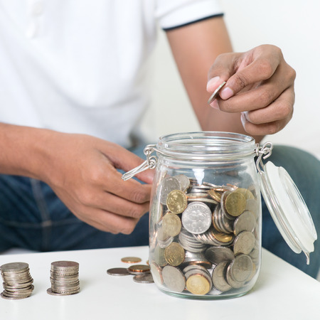 money jar: Savings concept. Focus on hand. Indian guy save money to glass jar. Stock Photo
