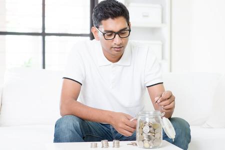 planificacion: Concepto de planificación financiera. Chico indio ahorrar dinero al frasco de vidrio. Hombre asiático que se sienta en el sofá en interiores. Modelo masculino hermoso. Foto de archivo