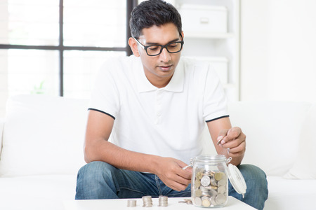 Financial planning concept. Indian guy saving money to glass jar. Asian man sitting on sofa indoor. Handsome male model. Stock Photo