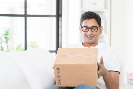 deliver: Courier delivery concept. Indian guy received an express parcel and checking the box at home. Asian man sitting on sofa indoor. Handsome male portrait.