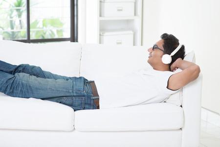bonhomme blanc: Guy indienne en appréciant la musique à la maison. Homme asiatique avec un casque d'écoute à la chanson, détendu et couchée sur le canapé à l'intérieur. Beau modèle masculin.
