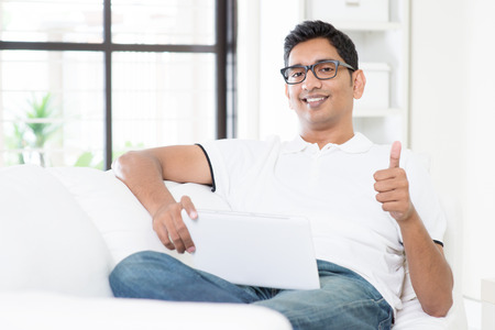 Portrait of Indian guy giving thumb up while using digital tablet computer at home. Asian man relaxed and sitting on sofa indoor. Handsome male model. Imagens