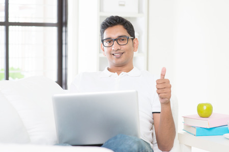 Indian guy with laptop computer working from home and giving thumb up. Asian man using internet indoor, relaxed and sitting on sofa. Handsome male model.