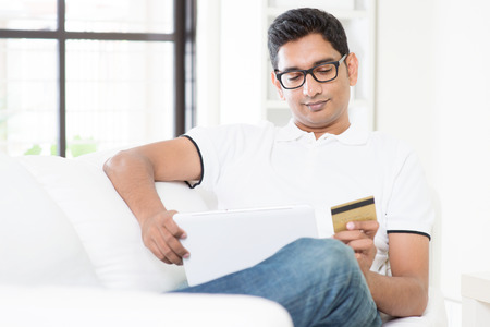 handsome: Indian guy hand holding credit card, enjoying internet online shopping using digital computer tablet at home. Asian man relaxed and sitting on sofa indoor. Handsome male model.