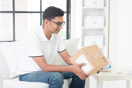 parcel: Courier delivery concept. Indian guy received an express parcel and checking the box at home.